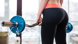 Back view of attractive young sportswoman training with barbell in gym