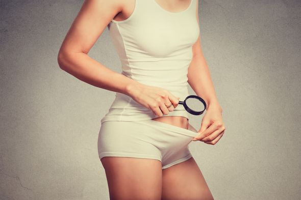 attractive slim woman looking with a magnifying glass on her pubic hair on the crotch