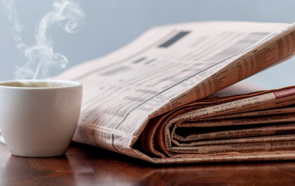 Newspaper and cup of coffee on wood table