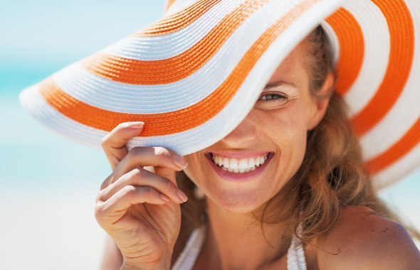 Portrait of happy young woman in swimsuit and beach hat