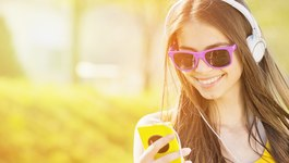Teenage girl with smartphone and headphones smiling