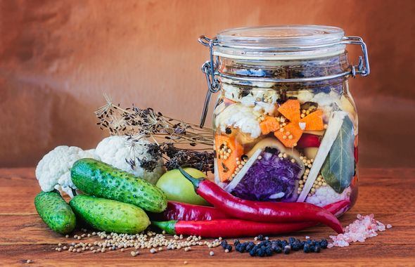 Jar of assorted brined lacto-fermented pickles on a wooden table surrounded by vegetables and spices.