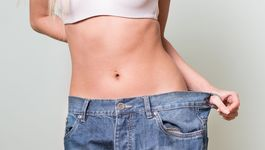 Close-up of a woman belly in a too big pants against grey background