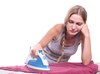 Bored sad young woman ironing clothes