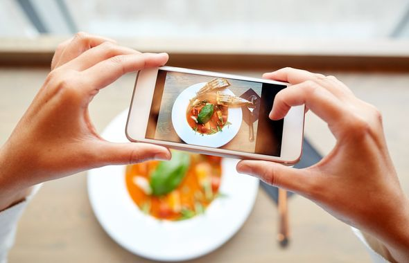 food, eating, technology, culinary and people concept - woman hands with smartphone photographing gazpacho soup at restaurant