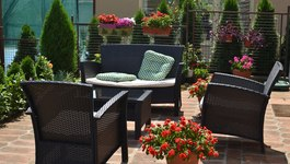 Set of brown garden furniture surrounded with garden plants and flowers