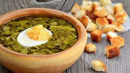 Sorrel soup with egg in bowl on wooden table