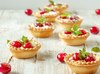 Tartlets with whipped cream and cherry on a white wooden background. Selective focus.