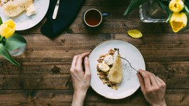 Top View Food Scene of Female eating Poached Pear Dessert on Rustic Dining Table