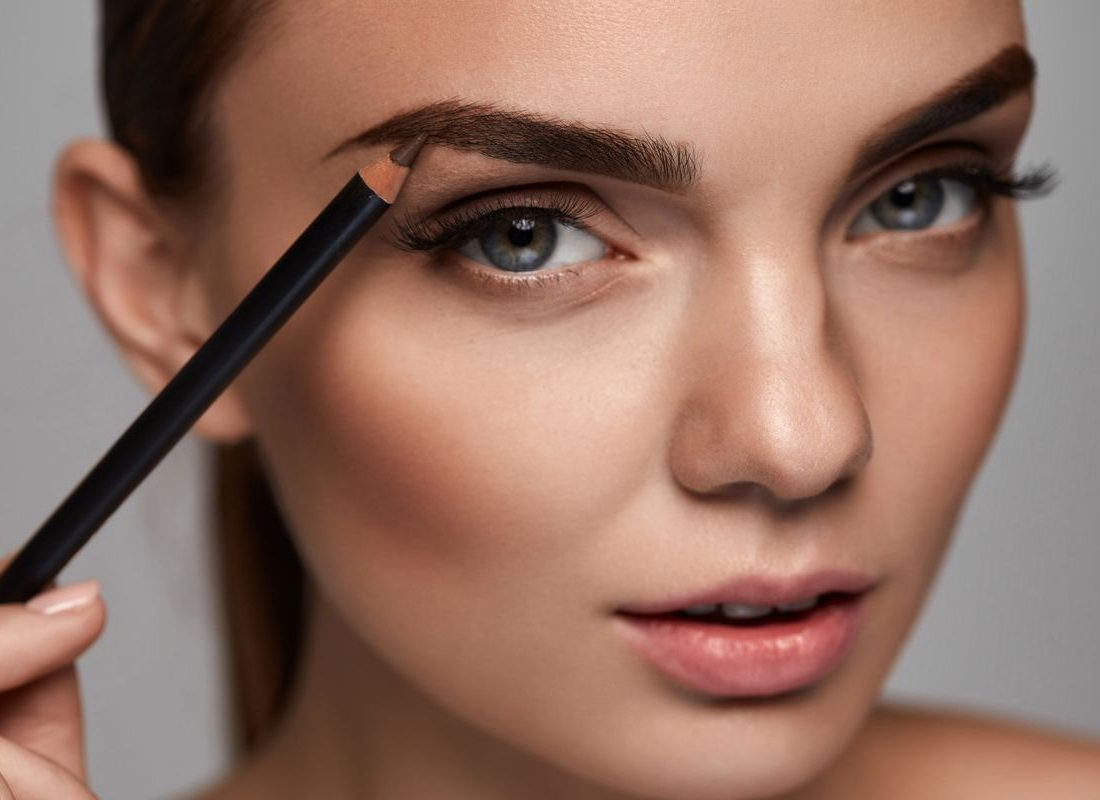 Piękna kobieta konturuje ołówkiem swoje brwi