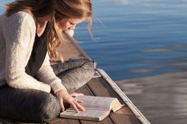 Dziewczyna czyta książkę na przystani