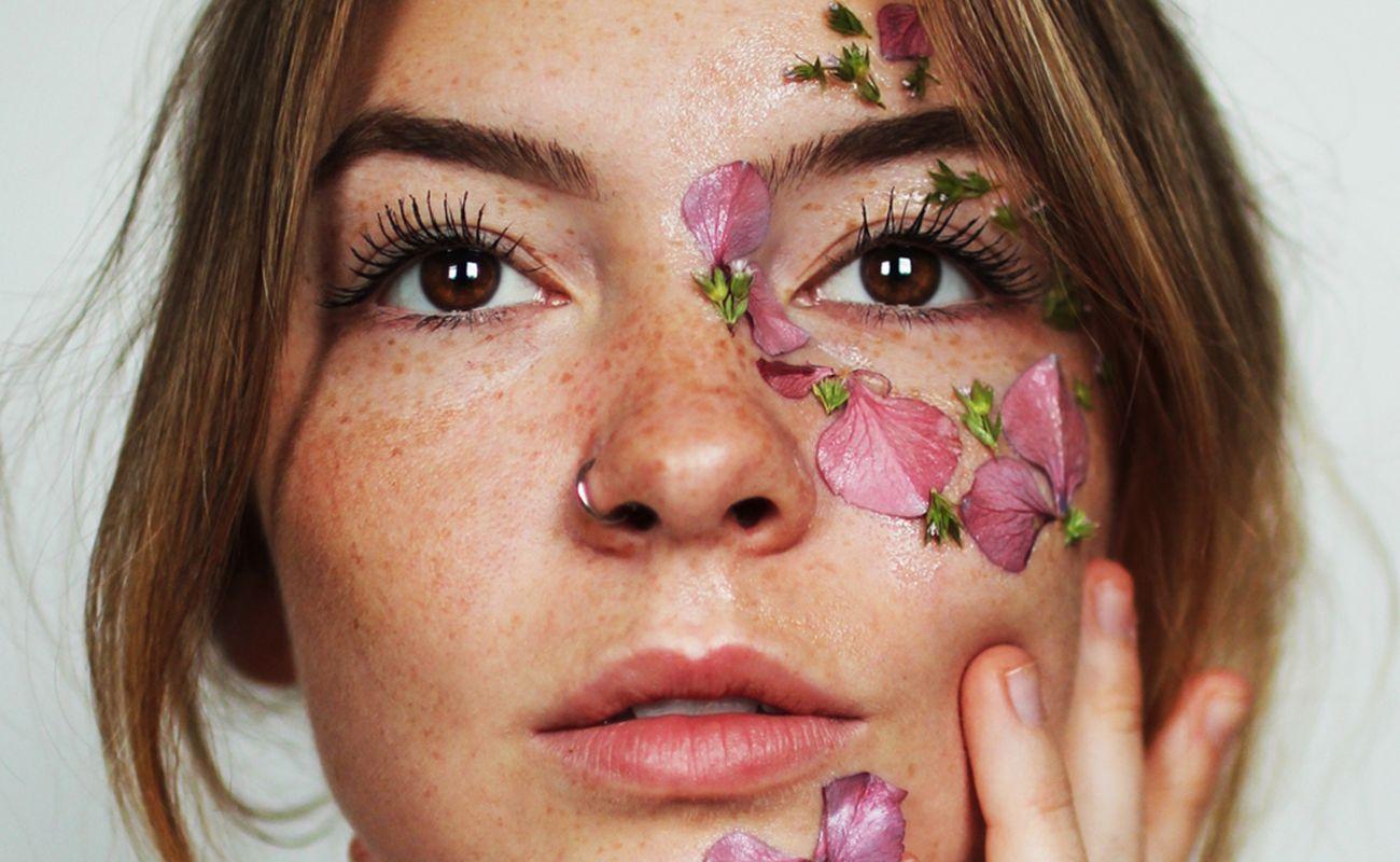 Kobieta z płatkami kwiatów na twarzy