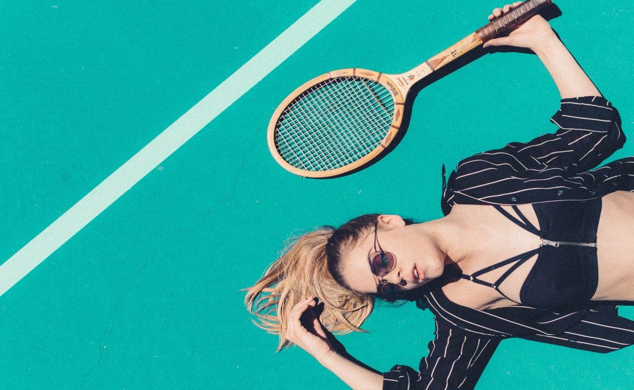 Dziewczyna leży na korcie tenisowych, obok niej rakieta