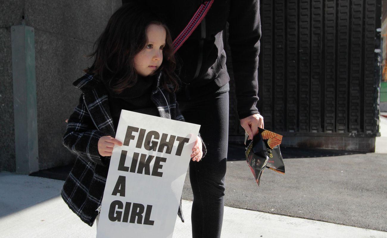 dziewczynka trzyma tablicę z napisem fight like a girl
