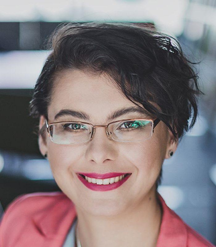 Elżbieta Jachymczak w fuksjowej szmince uśmiecha się do obiektywu