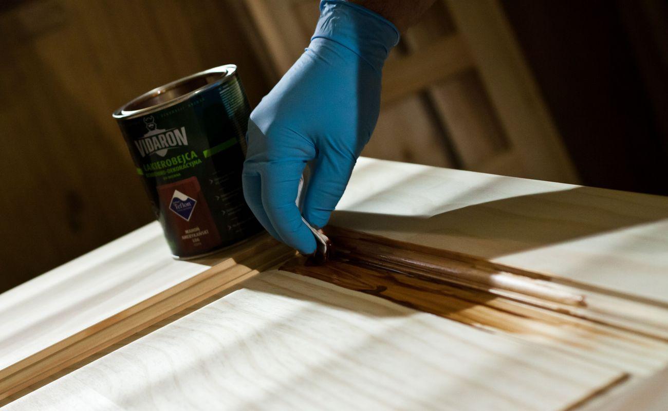ręka w niebieskiej rękawiczce impregnuje drewno
