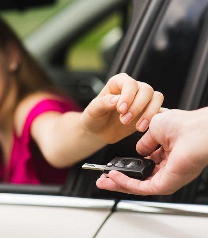 Kobieta odbiera kluczyki do nowego samochodu.