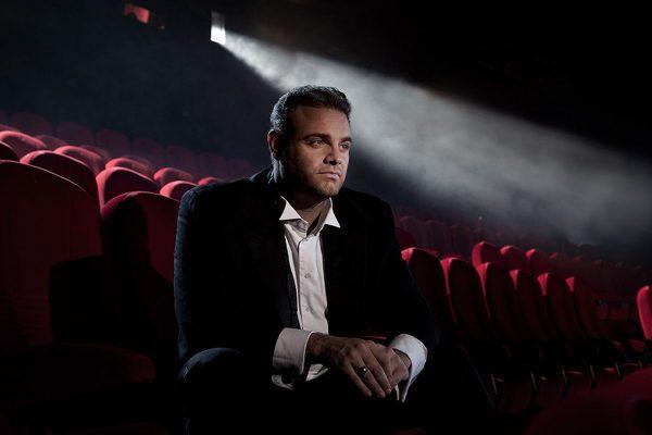 Joseph Calleja w białej koszuli i czarnym garniturze siedzący na widowni