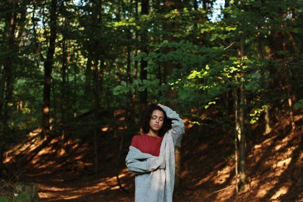 Kobieta w czerwonej bluzce i szarym swetrze, stojąca w lesie, który był inspiracją kolekcji Jesień 2018 marki KOKOworld