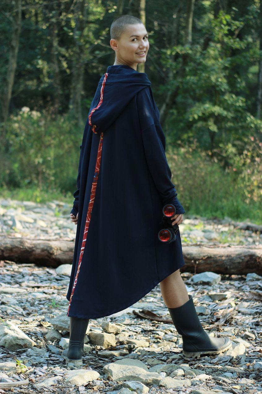 Młoda kobieta w długim, granatowym płaszczu na tle drzew