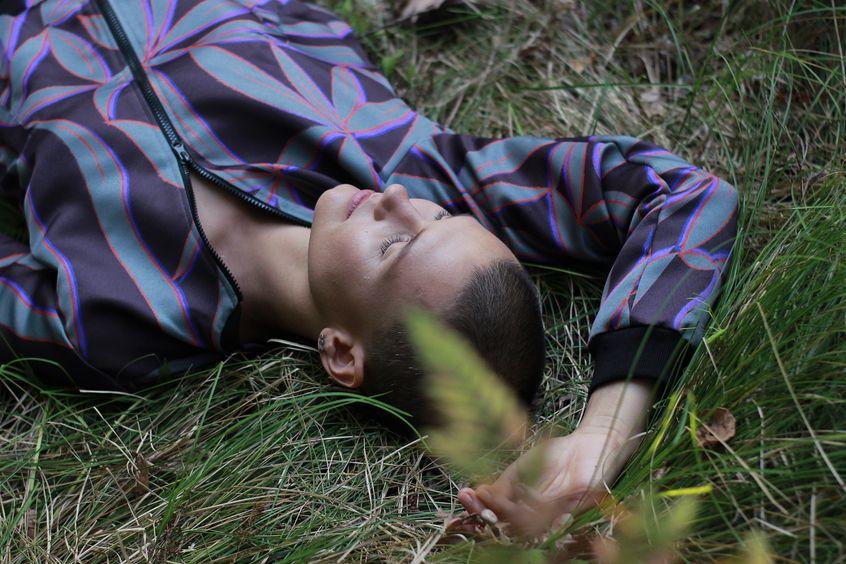 Kobieta w kolorowej bomberce, leżąca na trawie