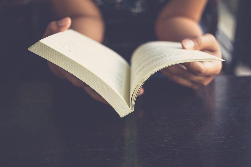 Kobieta czytająca książkę w wersji papierowej