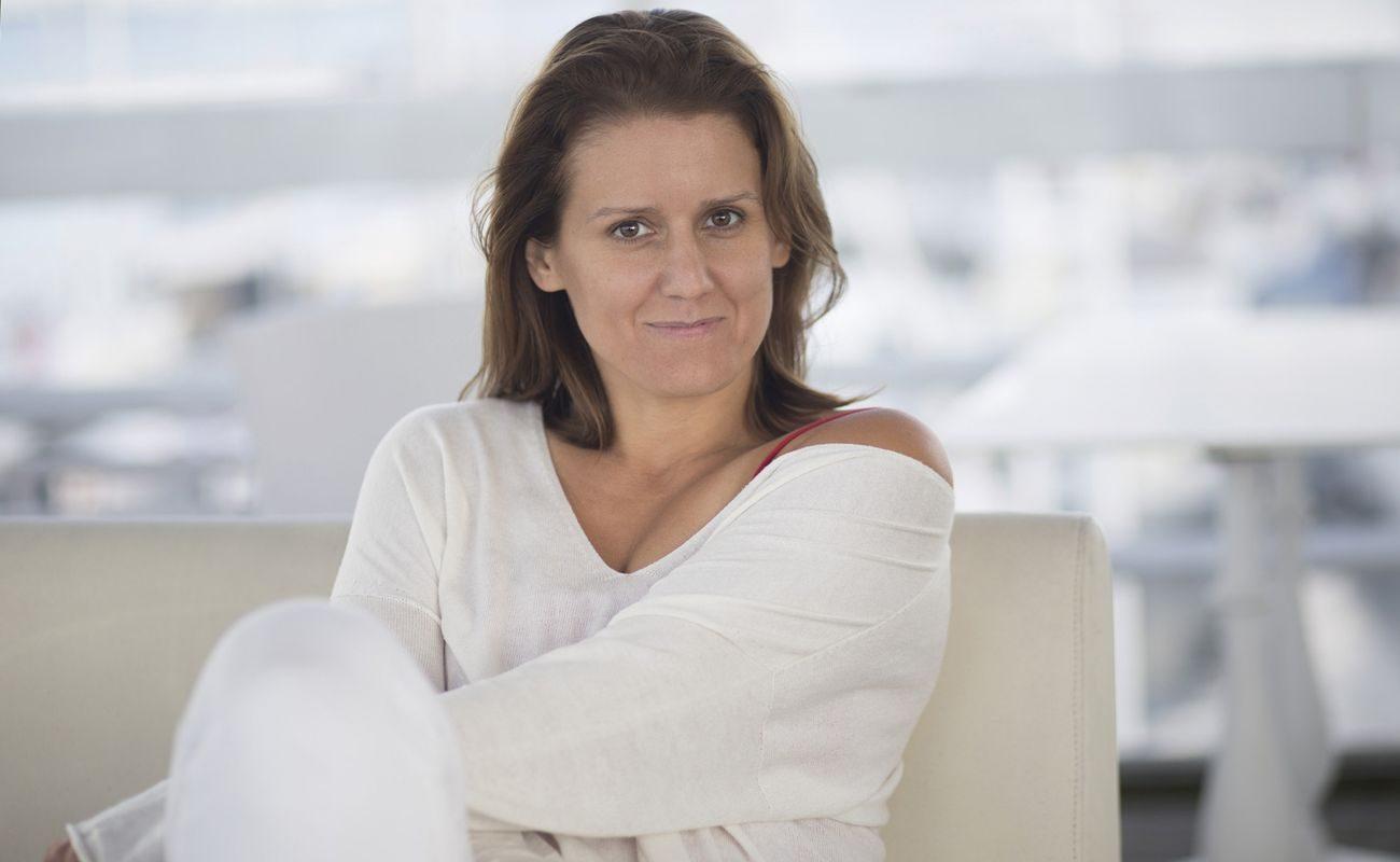 Małgorzata Majewska w białym stroju opiera się o białą kanapę