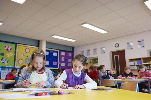 Sala lekcyjna i dzieci podczas pisania