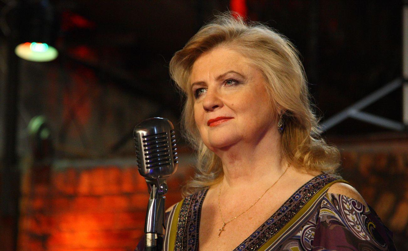 Stanisława Celińska pogodnie uśmiecha się ze sceny, na której stoi mikrofon