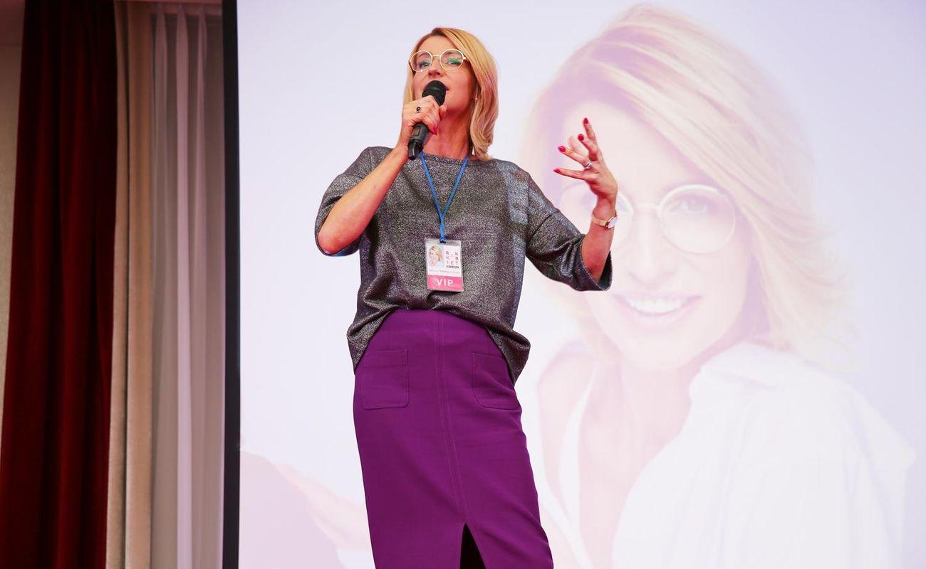 Tatiana Mindewicz-Puacz podczas Festiwalu Rok Kobiet 2018 stojąca na scenie w fioletowej spódnicy i szarej bluzce