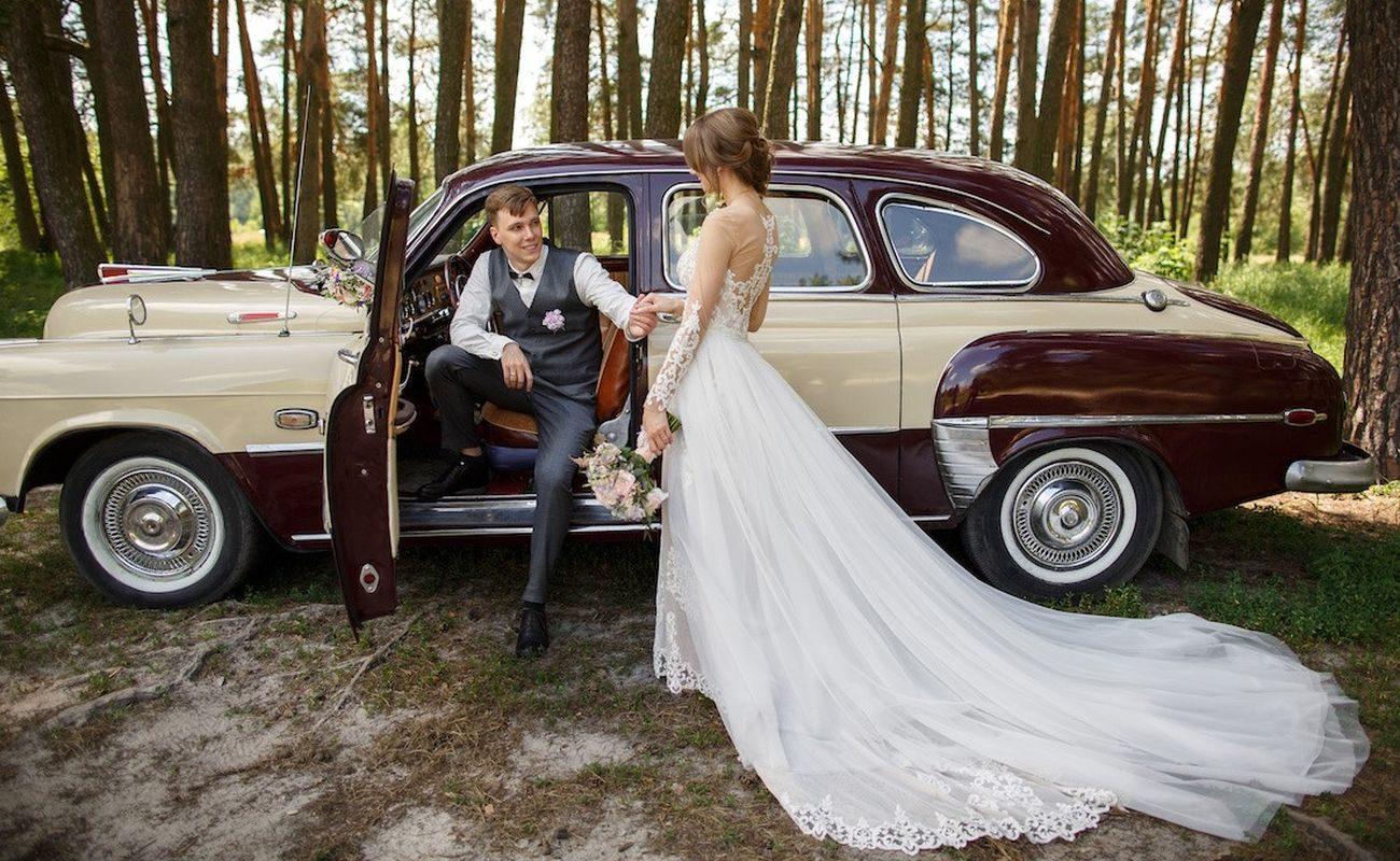 Młoda para pozująca na tle auta ślubnego