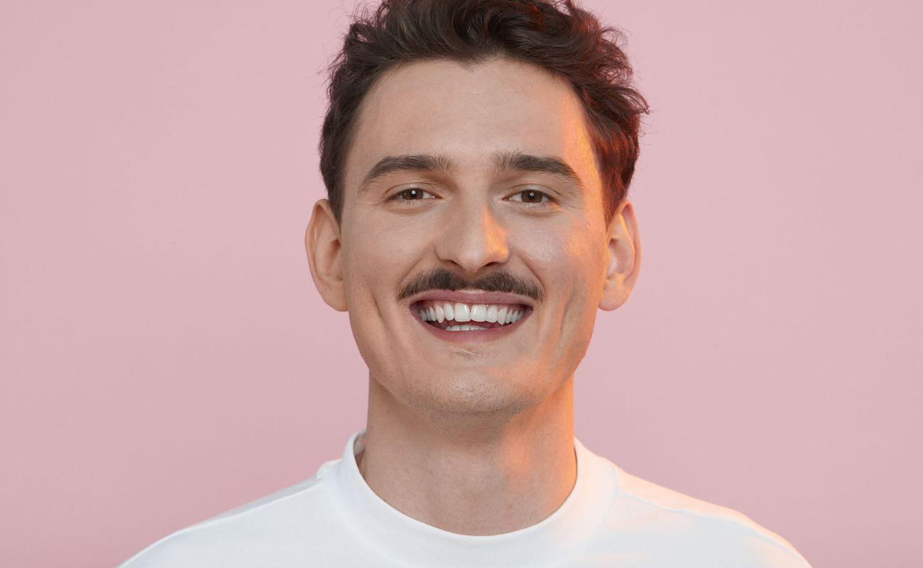 Uśmiechnięty Dawid Podsiadło na różowym tle
