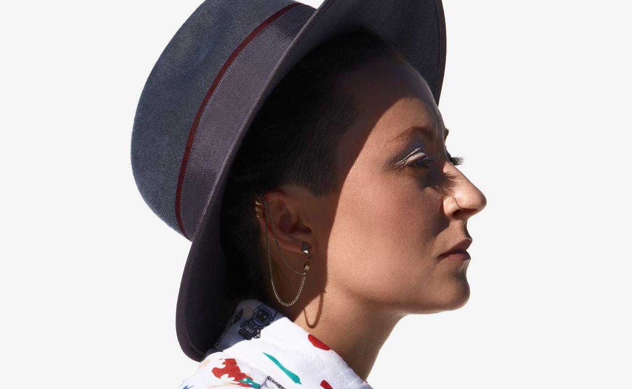 Natalia Przybysz ustawiona profilem w kapeluszu z rondem