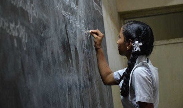 Jak porznać dobrego nauczyciela? Dziewczyna stoi pod szkolną tablicą
