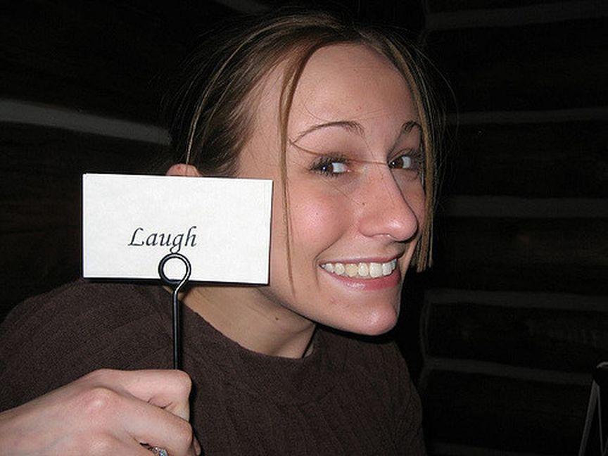 Kobieta uśmiechająca się z karteczką z napisem śmiech