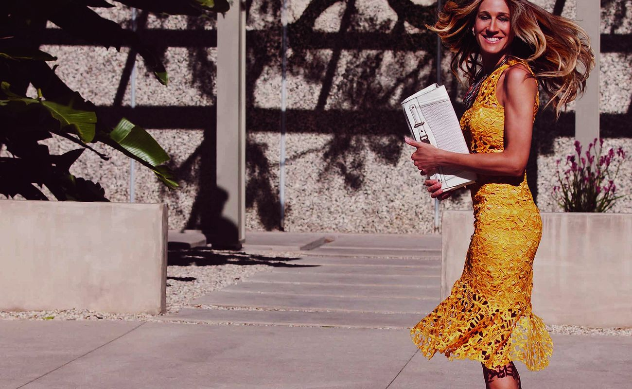 Sara Jessica Parker w żółtej sukience, trzymająca w dłoni torebkę
