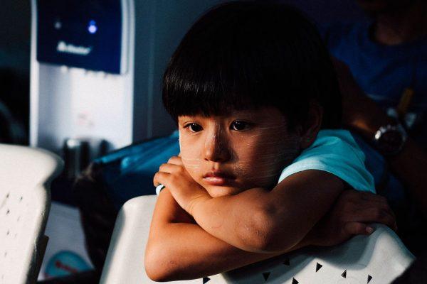 Smutny chłopczyk opierający się o oparcie krzesła. Być może jest ofiarą przemocy werbalnej