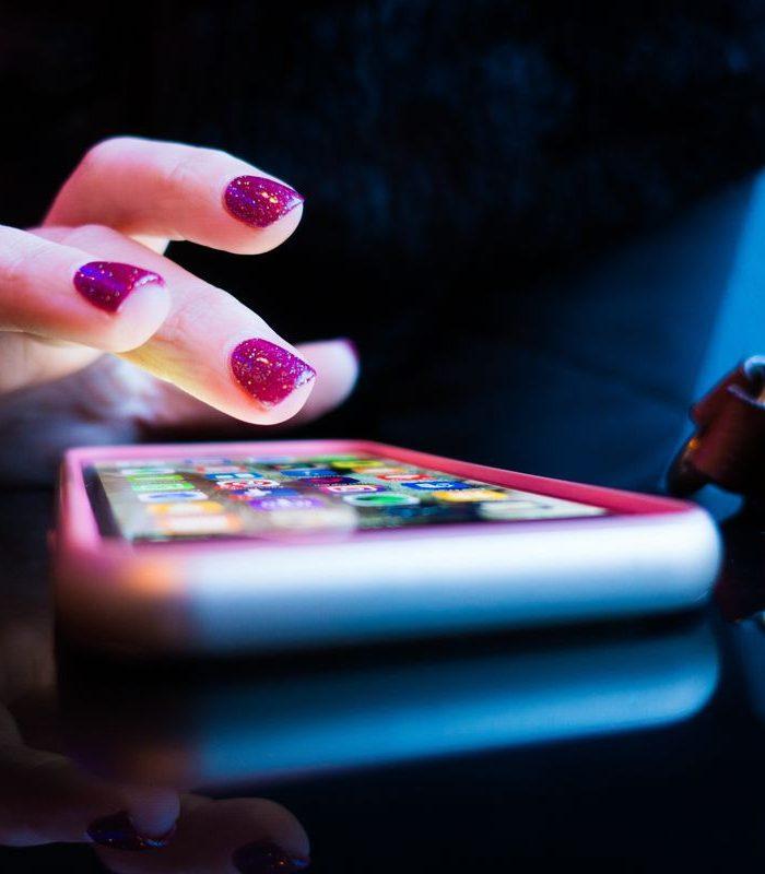 kobieta szukając aplikacji tinder w telefonie