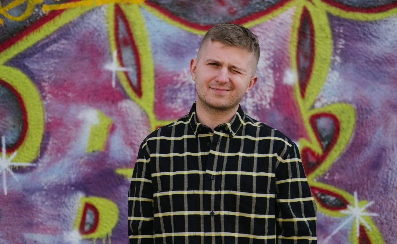 Maciej Marcisz to nie-pisarz, który swoją szczerością poruszy każdego. Maciej Marcisz na tle graffiti