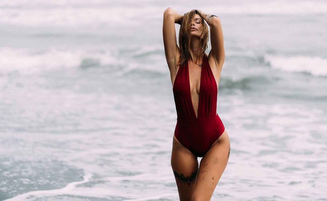 Kobieta o zgrabnej sylwetce idąca plażą