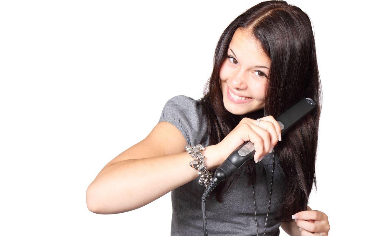 Kobieta prostująca włosy przy użyciu prostownicy