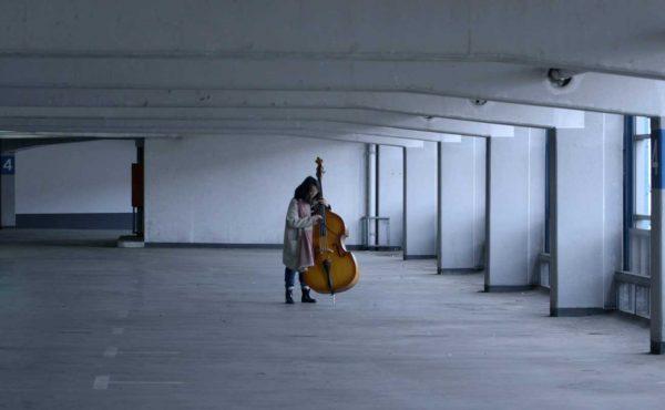 Dziewczyna z wiolonczelą na pustym parkingu