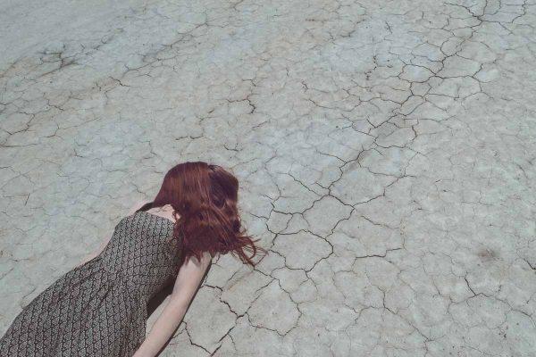 kobieta leżąca na popękanej ziemi